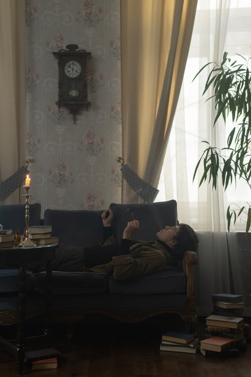 Man in Black Shirt Lying on Black Couch