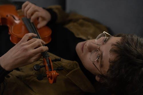Man in Brown Coat Playing Violin