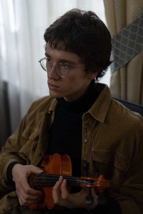 Man in Brown Jacket Holding Brown Acoustic Guitar