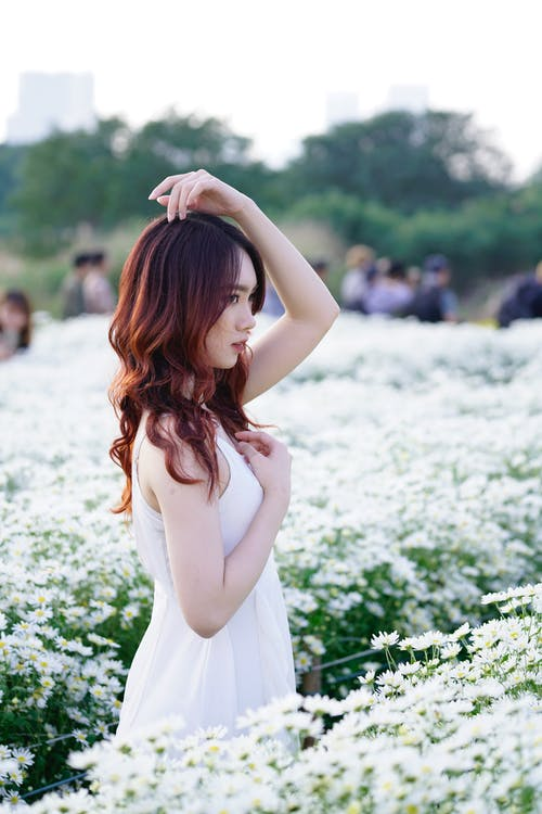 Side view of tender ethnic teenager in white dress touching wavy hair while looking away in field with blossoming flowers