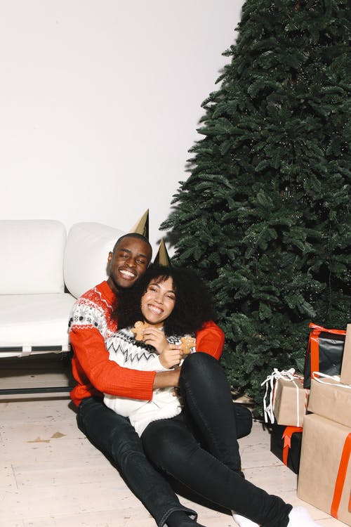 A Happy Couple Sitting Beside A Christmas Tree