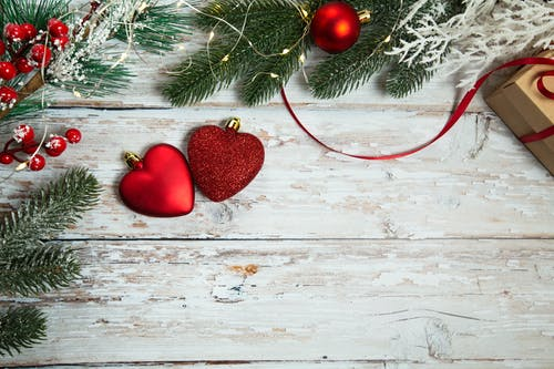 Top view festive composition of red shiny hearts placed on shabby plank surface near fir branches and gift box