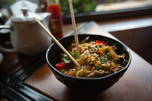 Bowl of delicious noodles with meat and vegetables served on table