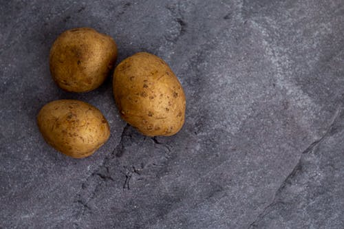 Top view of whole unpeeled potatoes placed on rough gray marble table in kitchen