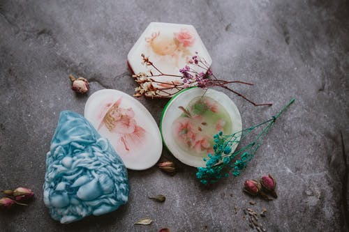 Top view of creative aromatic handmade soaps arranged on gray surface with colorful dried flowers and herbs