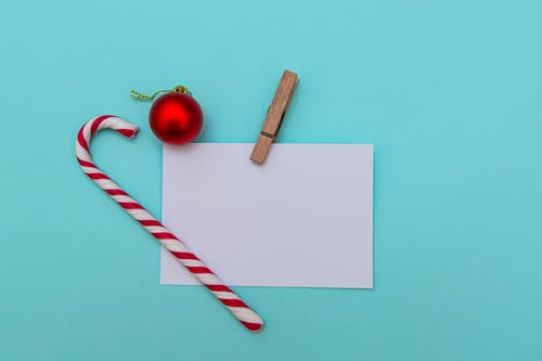 Top view of Christmas candy cane and red bauble on blue table composed with blank paper greeting card pinned with wooden clip