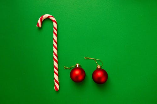 Top view pair of red shiny Christmas balls composed with candy cane on green background