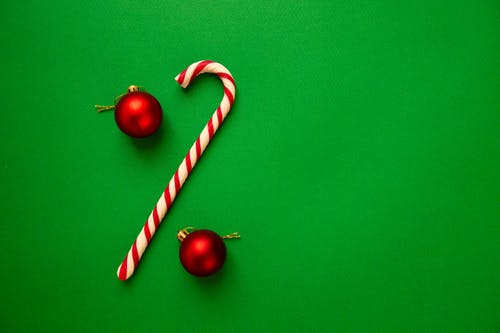 Red Christmas balls with candy stick on green background