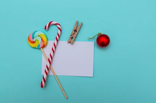 Blank paper sheet with clip arranged with Christmas ball and candies