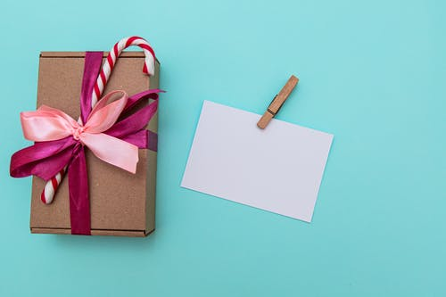 Blank postcard with clip arranged with present box decorated with candy cane