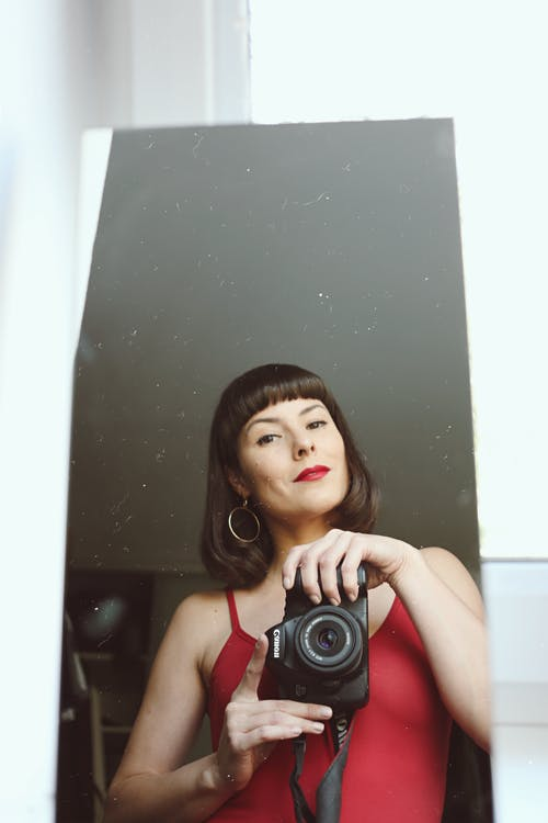 Woman in Red Tank Top Holding Black Camera