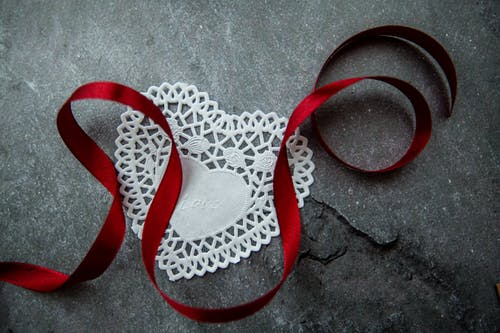 Top view of white heart shaped paper doily with Love inscription and red satin ribbon placed on gray stone tabletop