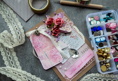 Top view of handicraft greeting card decorated with artificial flowers and fancy stones placed on table near box of colorful beads and buttons and tape lace