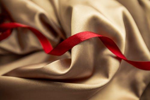 Red satin ribbon on golden silk cloth
