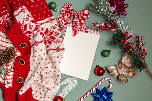 Christmas decorations and blank notepad arranged with knitted cardigan
