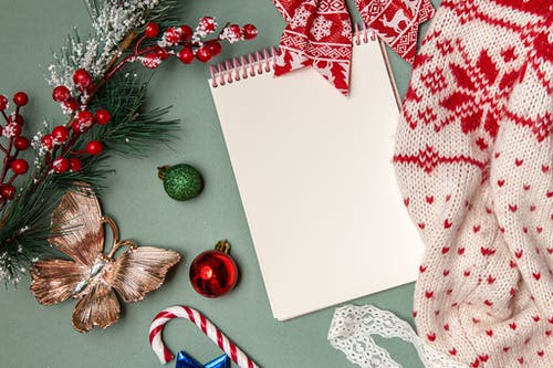 From above of empty spiral notebook with warm knitted sweater composed with various Christmas decorations and candy cane