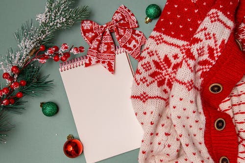 Notepad placed on table near warm sweater and Christmas decorations