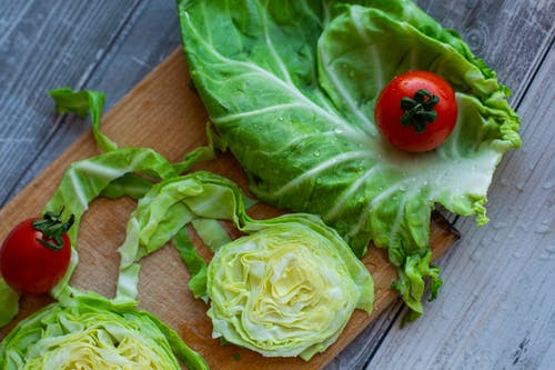 Fresh raw cabbage and tomatoes on wooden chopping board