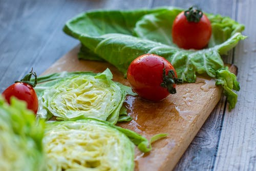 From above of appetizing ripe red tomatoes and cut fresh cabbage placed on wet wooden chopping board in kitchen