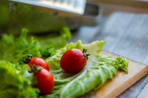 Cutting board with fresh salad leaves and tomatoes placed on table near grater