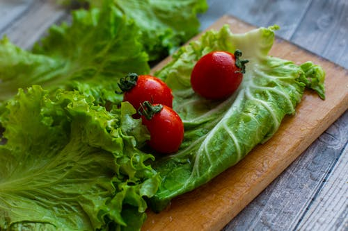 From above of various fresh lettuce leaves and ripe tomatoes placed on wooden chopping board on table in kitchen
