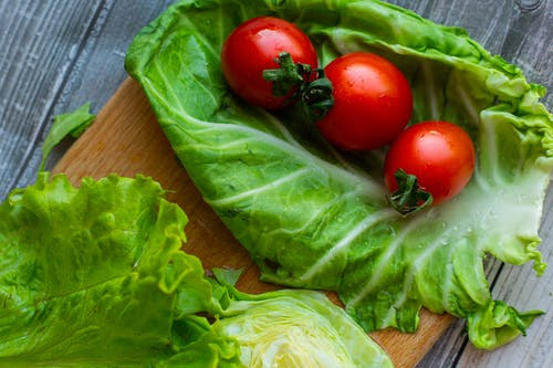 Fresh green leaf lettuce and bright red tomatoes arranged on table