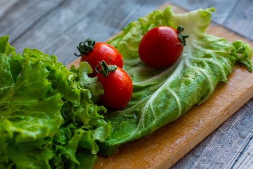 Washed tomatoes and lettuce leaves with water drops arranged on cutting boards