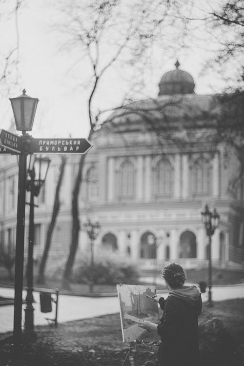 Back view of black and white unrecognizable female artist in warm clothes painting on canvas easel standing in city park near Odessa Opera House in autumn