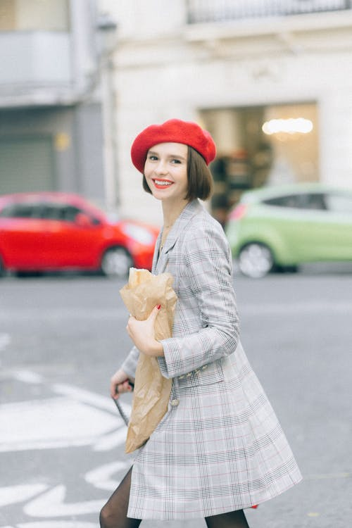 Woman in Red Hat and White and Gray Long Sleeve Dress Holding Brown Dog