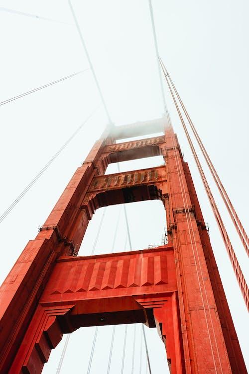 From below of famous red Golden Gate Bridge hidden under foggy sky in San Francisco