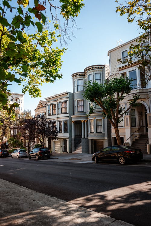 Various cars parked on asphalt road near classic styled residential houses against cloudless blue sky in San Francisco