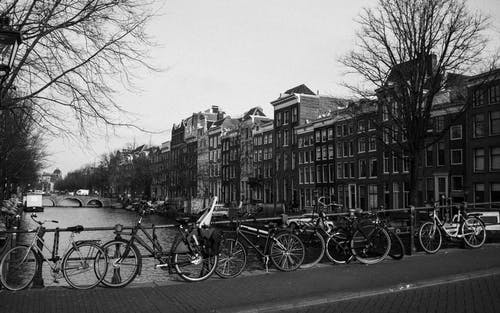 Black and white of various bicycles parked on paved bridge over rippling canal near aged typical residential buildings in Amsterdam