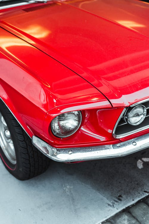 From above fragment of elegant red vintage car with shiny surface and round headlights parked on street on sunny day