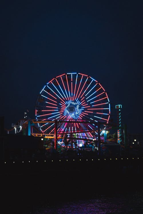 Illuminated Ferris wheel in amusement park at night