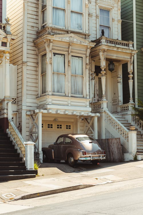 Old fashioned car parked near aged classic house