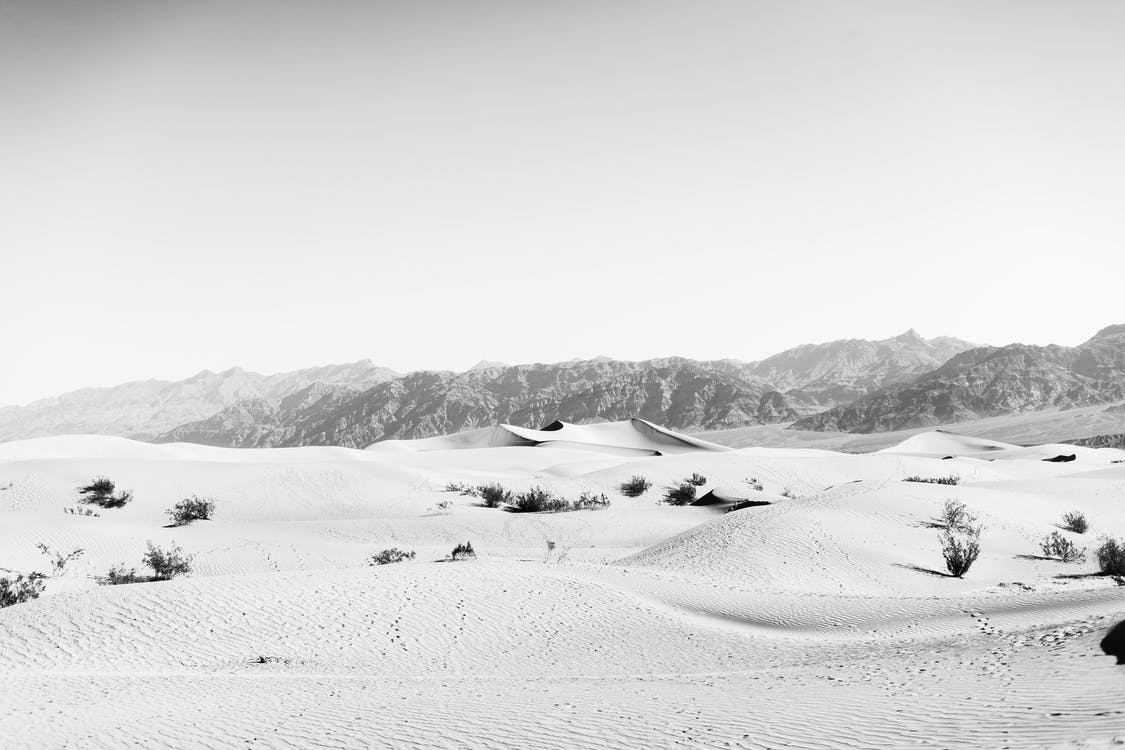 Picturesque black and white scenery of desert with sandy dunes surrounded by rocky hills on sunny day