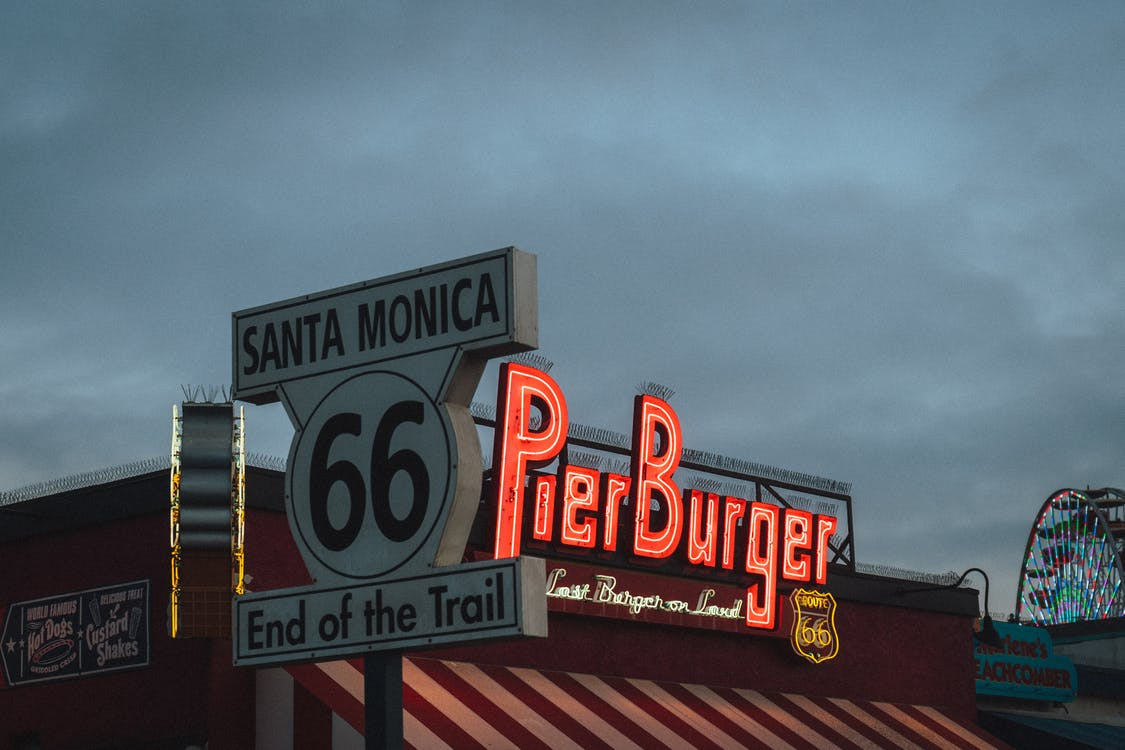 Low angle of road sign with Route 66 End of the Trail inscription located near fast food restaurant against cloudy evening sky on Santa Monica Beach