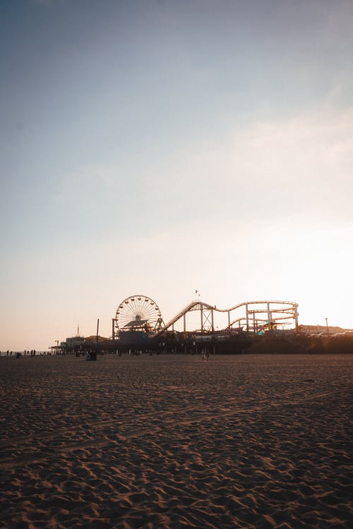 Amusement park on sandy beach at sundown