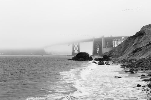 Breathtaking black and white scenery stormy ocean with foamy waves washing rocky beach near famous Golden Gate Bridge hidden under thick fog in San Francisco