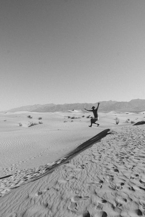 Anonymous guy jumping on sandy dunes in desert