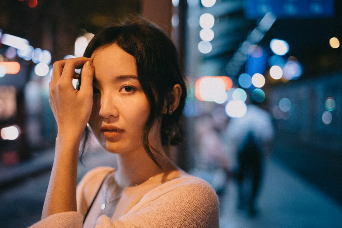 Young Asian woman touching face on street
