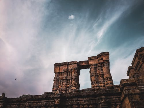 Architectural details of old Hindu temple under cloudy sky
