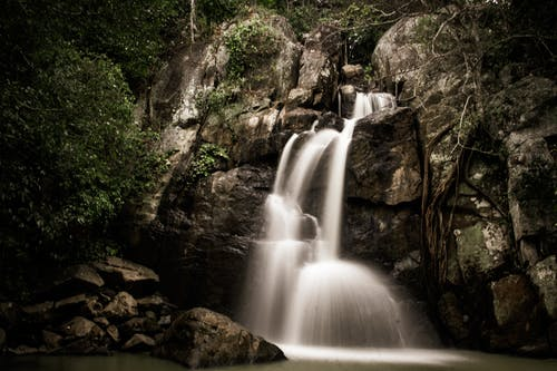 Magnificent scenery of rapid Midubanda Waterfall streaming through massive rocky cliff in green forest in daytime