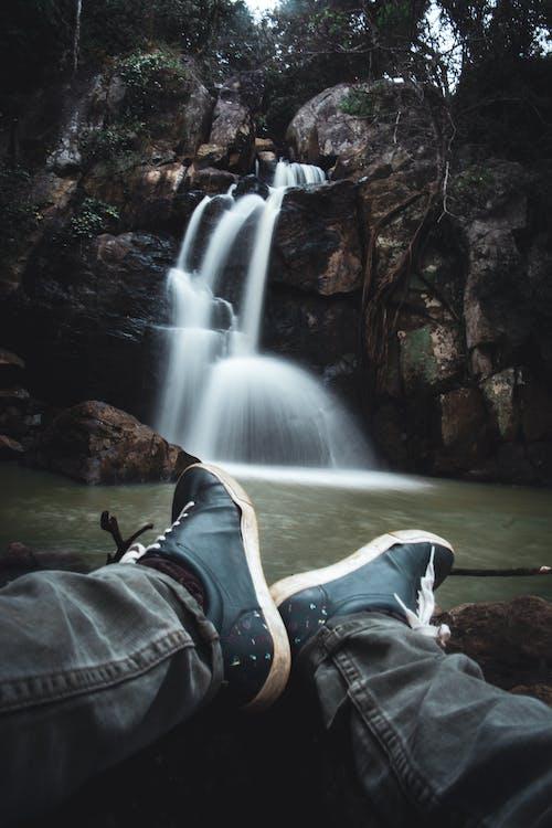 Unrecognizable tourist resting near pond and enjoying amazing waterfall