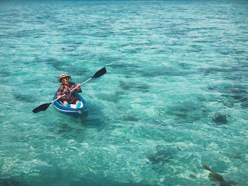 Man in Blue Shirt Riding on Blue Kayak on Body of Water