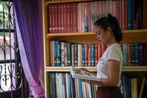 Woman Reading a Book beside Book Shelves