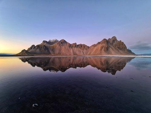 岩の島の近くに氷河がある穏やかな湖