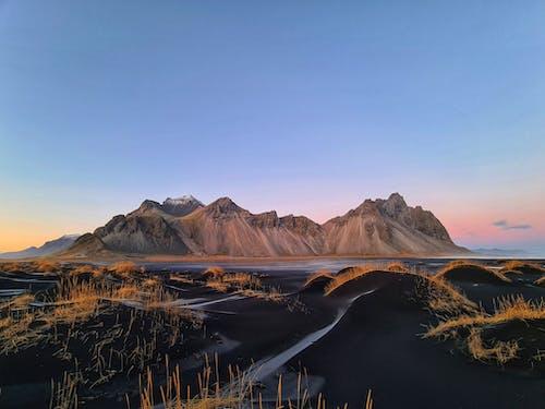 草が茂った丘のある静かな山岳地帯の上の夕日の風景