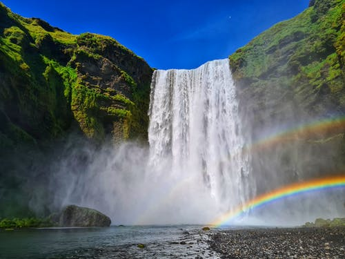 Rainbows on waterfall flowing from high green mountains