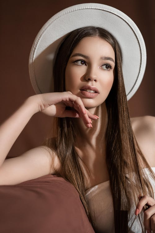 Charming teenager in hat resting on sofa on brown background